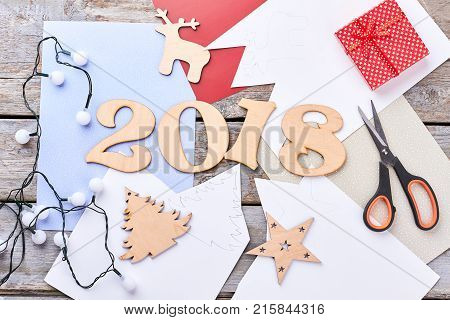 Handmade wooden number 2018. Carved wooden digit 2018 for New Year, wooden New Year figures, scissors, paper, Christmas lights, gift box. Handmade New Year 2018 craft.