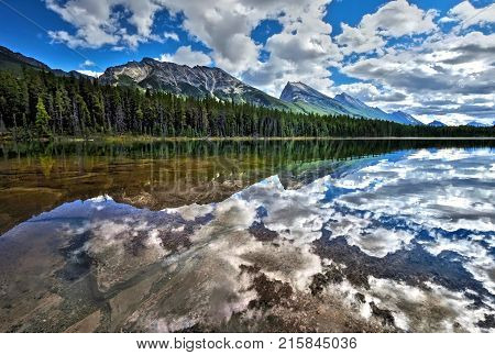 Honeymoon lake surronded by forest and mountains. Beautiful reflections in crystal clear water of Endless Chain Ridge in Canadian Rockies. Jasper National Park. Alberta. Canada.