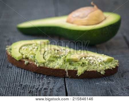 Two slices of bread from wheat flour smeared with cream of avocado with herbs. A vegetarian diet. A healthy way of life.