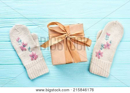 Gift box and pair of female knitted mittens. Beautiful pair of woman white woolen gloves and handmade box with present tied with golden satin ribbon. New Year and Christmas holidays.