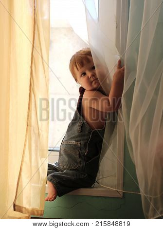 Cute llittle barefoot baby with ginger hair in jeans overall looking out the organza curtains standing on knees at the window sill. poster