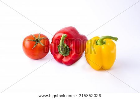 Red peppers and yellow peppers with tomatoes on a white background. Fresh vegetables on a white background. Composition from vegetables. Red and yellow peppers on white background with tomato. Tomato with peppers on a white background.