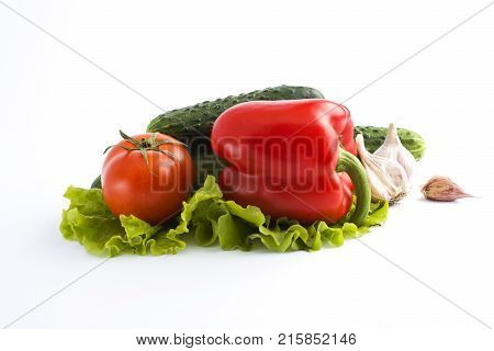 Red peppers and yellow peppers with tomatoes on a white abackground. Fresh vegetables on a white background. Composition from vegetables. Red and yellow peppers on white background with garlic. Tomato with peppers and cucumber on a white background.
