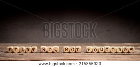 Business or New Year resolution concept with small wooden dices and the words Start now not tomorrow