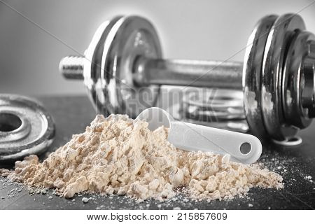 Heap of protein powder with scoop and dumbbell on table, closeup
