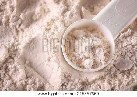 Protein powder and scoop, closeup