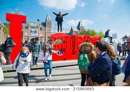 Amsterdam, Netherlands - April 20, 2017: Rijksmuseum and Statue I am Amsterdam at day, Netherlands