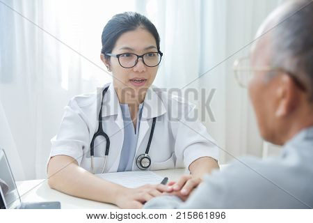 Young Asian Female doctor reassuring senior male patient with holding hands in medical office.