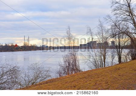 Early spring park on coast of Neva River at cloud day Russia.