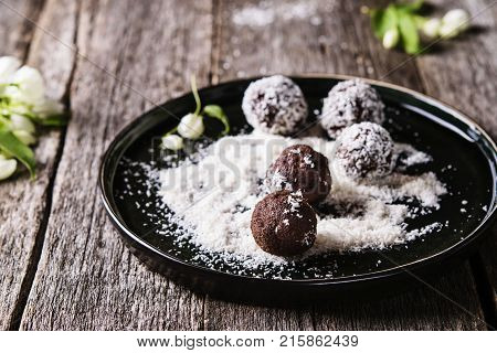 Homemade healthy vegan chocolate balls, truffles, candies sprinkled grated coconut in the plate on the vintage wooden table. Selective focus