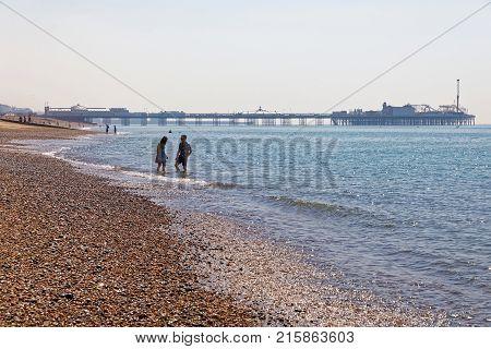 BRIGHTON GREAT BRITAIN - JUN 17 2017: Sunbathing people on the Brighton beach Brighton pier in the background. June 17 2017 in Brighton Great Britain