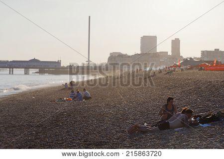 BRIGHTON GREAT BRITAIN - JUN 17 2017: People at on the Brighton beach at sunset Brighton pier in the background. June 17 2017 in Brighton Great Britain