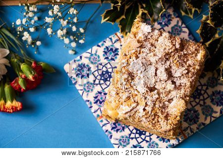 Slice of Cake Napoleon with sour cream. Layered puff pastry napoleon cake with powdered sugar and butterscotch frosting on blue decoration background. Sweet dessert food