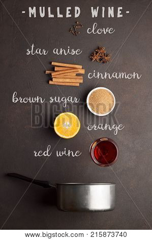 Ingredients for recipe of mulled wine with text on brown stone background. Wine orange sugar cinnamon star anise and clove for cooking gluhwein in pot.