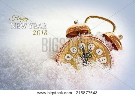 new year 2018 concept vintage alarm clock in the snow shows five minutes before twelve text