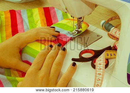 Workplace of tailor. people needlework and tailoring concept - tailor woman threading needle of sewing machine