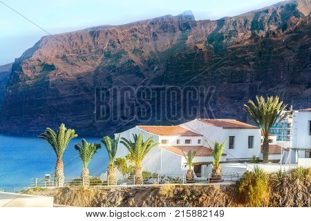 Traditional house architecture against Los Gigantes mountain illuminated by sunset light in Tenerife city Spain