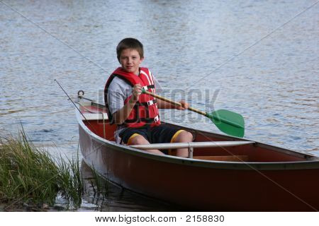 Boy Paddling A Canoe