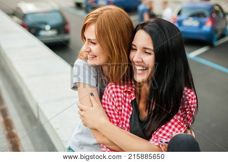 Two atractive young girls hugging, laughting and sitting near road in the street. one brunette girl in red plaid shirt, another redhead girl in gray shirt and blue skirt. concept of sincere friendship