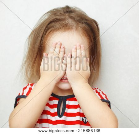 Cute little girl in striped T-shirt covers her face with palms and stands beside white wall. Child plays hide and seek portrait photo.
