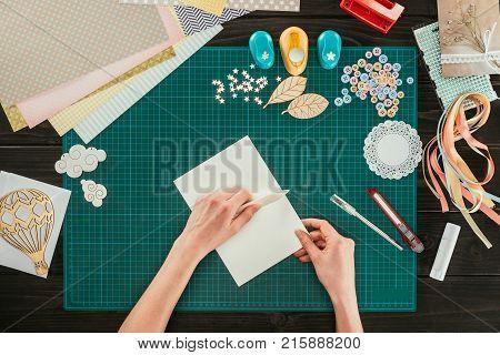cropped image of artist making greeting scrapbooking postcard