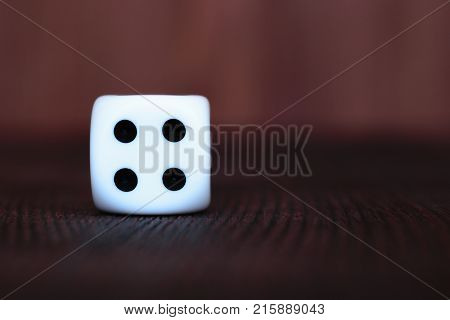 Single white plastic dice on brown wooden board background. Six side cube with black dots. Number 4.