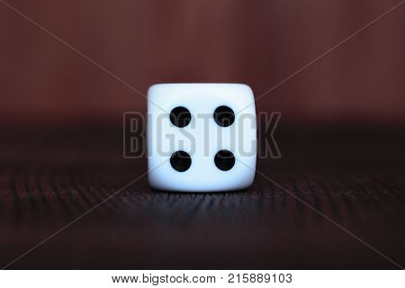 Single white plastic dice on brown wooden board background. Six side cube with black dots. Number four.