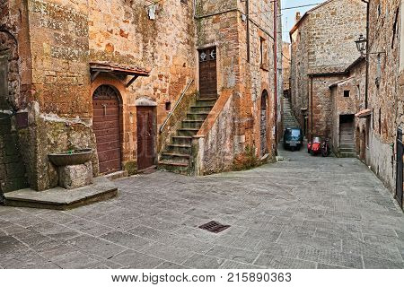 Pitigliano, Grosseto, Tuscany, Italy: picturesque old alley with ancient houses and drinking fountain in the medieval village
