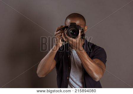 obscured view of african american photographer taking picture on photo camera