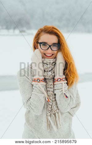 Charming smile of the beautiful young woman with red head wearing glasses, gloves and scarf during the snowfall in the countryside.