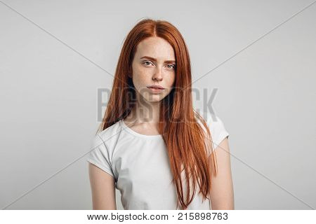 Indoor portrait of attractive young European ginger woman with freckled face and hair bun standing at grey studio wall, dressed in white blouse, her look and posture expressing self-confidence