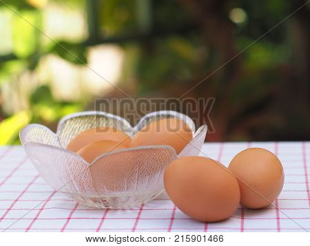 Two chicken eggs on check tablecloth and another three inside a flower glass bowl with blurry garden background.