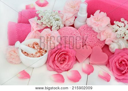 Ex foliation beauty skincare treatment products with Himalayan ex foliating salt, heart shaped soap, body scrub, body lotion, sponges, wash cloths, pink carnation flowers and decorative seashells.