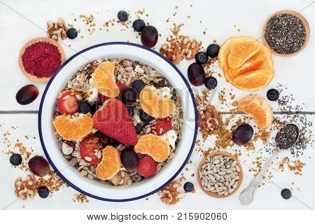 Healthy food for breakfast including granola, fresh fruit, nuts, pollen grain, yoghurt, acai berry powder and chia seed with foods high in omega 3, protein, antioxidants, anthocyanins and vitamins.