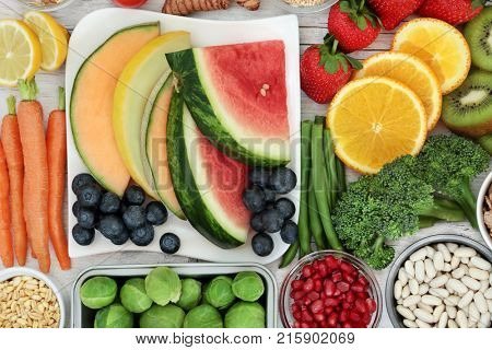 Healthy food nutrition concept with fresh fruit, vegetables, grain and pulses. Super foods high in antioxidants, anthocyanins, fiber, minerals and vitamins.
