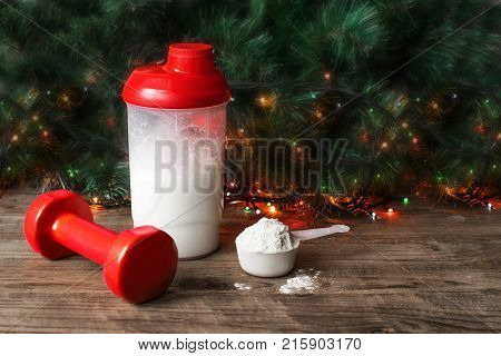 Whey protein shaker. scoop and training dumbbell on christmas background. Sports nutrition
