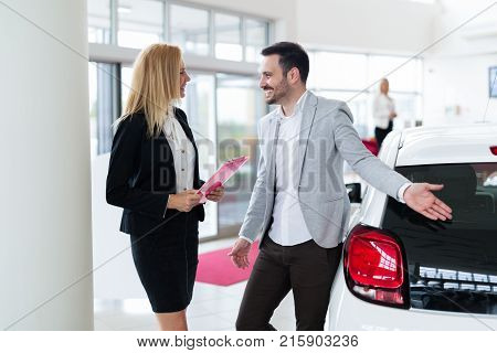 Professional salesperson selling cars at dealership to new buyer