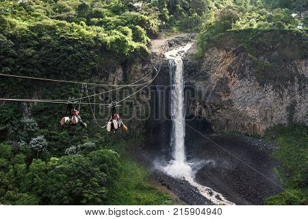 Cascades Route, Banos, Ecuador - November 28, 2017: Tourists Gliding On The Zip Line Trip Against Br
