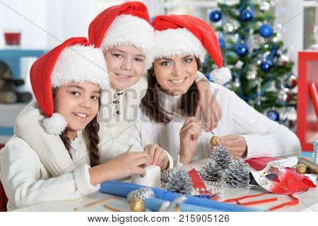 Portrait of ypung mother and her children  making  Christmas decorations sitting at the table