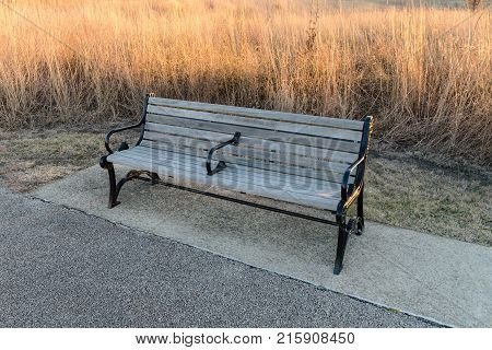a park bench off the walking trail on a sunny fall morning