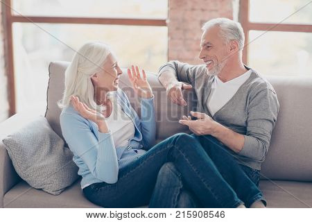 Happy Senior Couple Having Fun, Looking To Each Other, Laughing, Sitting In Living Room, Woman's Leg