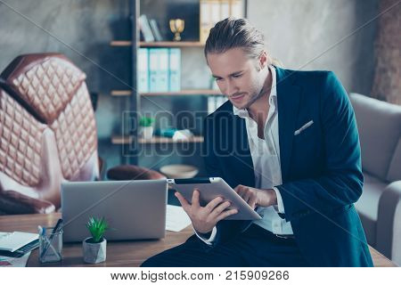 Portrait Of Attractive Rich Businessman  Sitting On Table In  Workstation, Using Tablet For Work