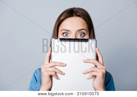 Young, Shocked  Girl With Half Face And Wide Opened Eyes Peering Out Laptop, Holding Tablet In Two H