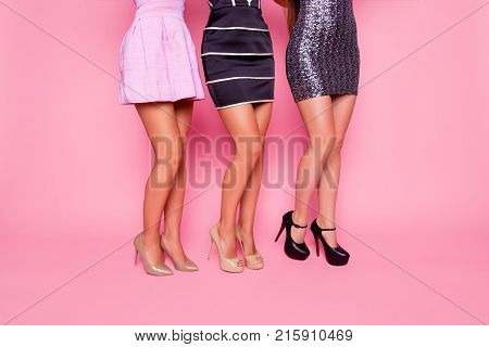 Side View Portrait Of  Three Beautiful Girls In Dress Showing Their Smooth Legs On Pink Background