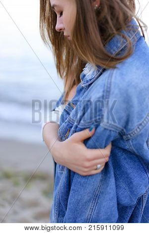 Shooting close-up portrait of wonderful young woman who stares into distance at sea waves and flirtatiously beckons with look, poses and smiles, enjoys fresh air, standing on shore of blue bottomless sea on summer sunny evening. Woman of European appearan