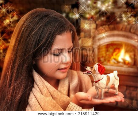A little happy dog Jack Russel Terrier Santa Claus on a beautiful girl's hands near burning fireplace at Christmas night. Xmas New Year holidays fairy tale magic 2018 Year of the Yellow Dog