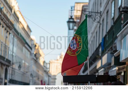 National Flag inside Exhibitor and Rua Augusta Arch in background in Lisbon Shop Portugal