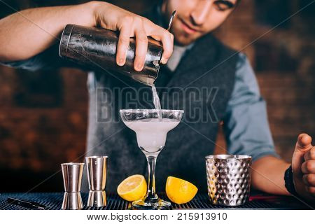 Professional Bartender Pouring Margarita Cocktail With Strainer And Cocktail Tools