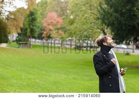 Young mulatto guy satisfying with receiving approving message from sweetheart to date in park. Cute boy dressed in black coat waiting for lovely friend in park. Concept of romantic gladden moments and park strolling.