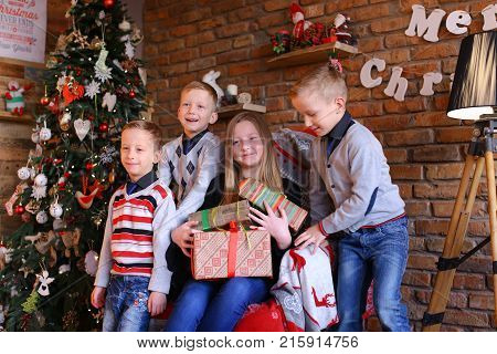 Happy brothers boys and sister waving their palms on camera smiling in good mood. European-looking girl holds hands many boxes of Christmas presents given by beloved eve holidays. beautiful female blond child dressed blue jeans, shirt black cardigan. Litt